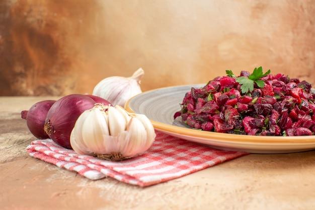 Salada de vegetais vermelha com foco seletivo em um prato com cebola roxa e alho à esquerda em um fundo claro com espaço de cópia