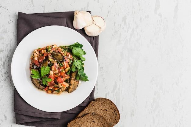 Salada de verão de berinjela e tomate em um prato branco