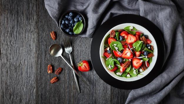 Salada de verão de morangos, mirtilos, espinafre, noz-pecã e queijo feta esmigalhado em uma tigela branca sobre uma mesa de madeira escura com um pano cinza, vista horizontal de cima, horizontal, espaço livre