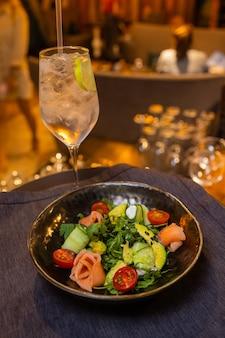 Salada de verão em um prato branco com um garçom na mão.