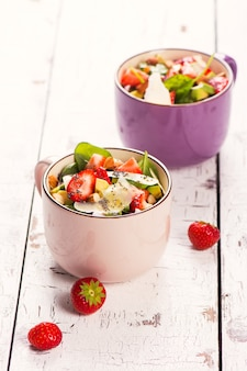 Salada de verão fresco com morango, abacate e espinafre no fundo de madeira rústico branco