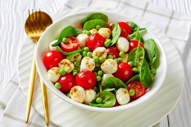 Salada de verão rápida fitness com ervilhas jovens, minibolinhas de mussarela, tomate cereja fresco de espinafre com molho de vinagre balsâmico em uma mesa de madeira branca com talheres, vista de cima, close-up