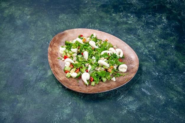 Salada de verduras de legumes em um prato elegante com fundo azul escuro