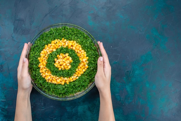 Salada de verduras de vista superior com calos dentro de uma placa de vidro redonda sobre a mesa azul escura.