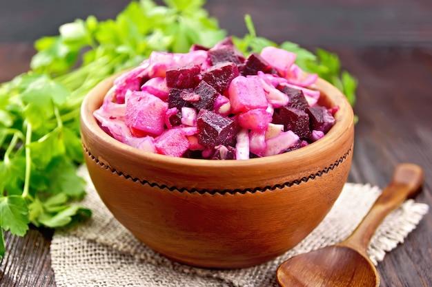 Salada de vinagrete com conserva ou chucrute, batata, beterraba e cebola, temperada com óleo vegetal em uma tigela sobre serapilheira, salsa sobre fundo escuro de madeira