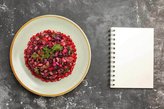 Salada de vinagrete com vista de cima com romãs e feijão na mesa cinza