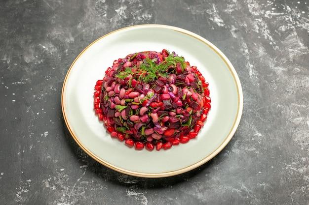 Salada de vinagrete de vista frontal com romãs e feijão no fundo escuro