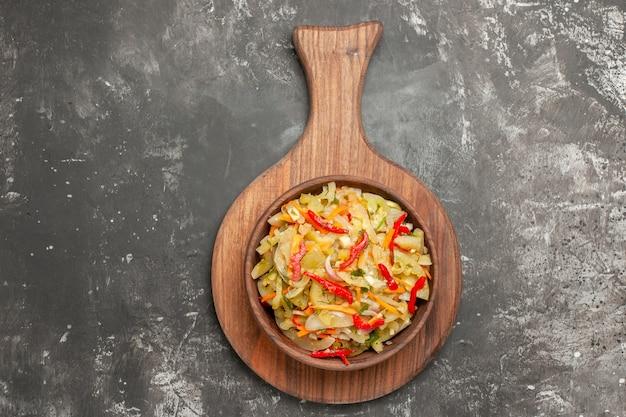 Salada de vista de cima em close-up uma salada de vegetais apetitosa na tigela na tábua de corte