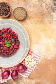 Salada de vista de cima em um prato cinza com pimenta preta moída de pimenta preta na parte superior e alho de cebola vermelha abaixo em um fundo de madeira com espaço para cópia