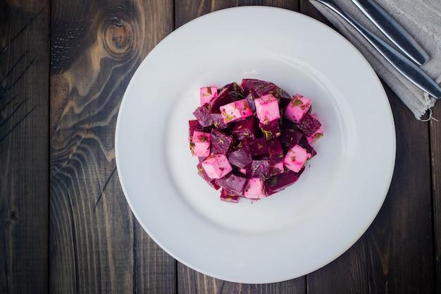 Salada de vista superior com beterraba e queijo feta no prato na mesa de madeira