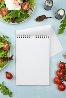 Salada de vista superior com ovo frito e tomate com caderno em branco