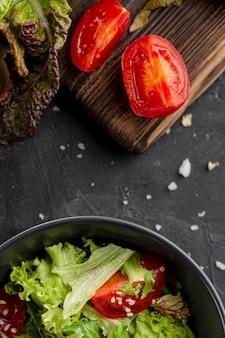 Salada de vista superior em uma tigela escura ao lado de tomate fatiado