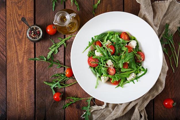 Salada de vitamina de tomate fresco, rúcula, queijo feta e pimentão. menu dietético. nutrição apropriada. vista do topo. postura plana.