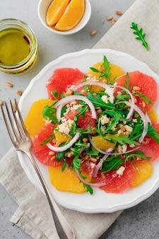 Salada de vitaminas cítricas. laranja, toranja, queijo ricota, pinhão, cebola roxa e rúcula com azeite de oliva em placa de cerâmica sobre concreto cinza ou pedra velha