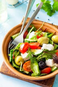 Salada de vitaminas de verão salada grega closeup com legumes frescos, queijo feta e azeitonas pretas