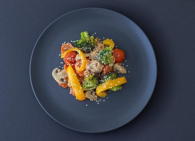 Salada deliciosa com vegetais maduros na mesa escura salada feita de brócolis, tomate cereja, cogumelos pimenta amarela e pedaços de peito de frango
