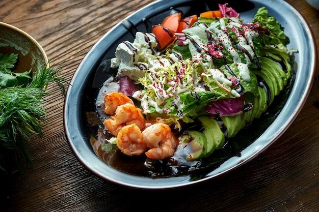 Salada deliciosa e dietética com camarão grelhado, queijo feta, tomate e abacate, servido em uma placa preta sobre uma mesa de madeira. comida de restaurante