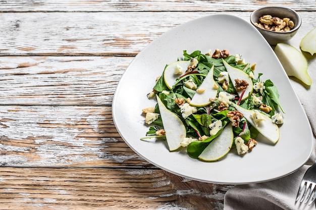Salada diet com queijo gorgonzola azul, peras, nozes, acelga e rúcula. fundo branco. vista do topo. copie o espaço.