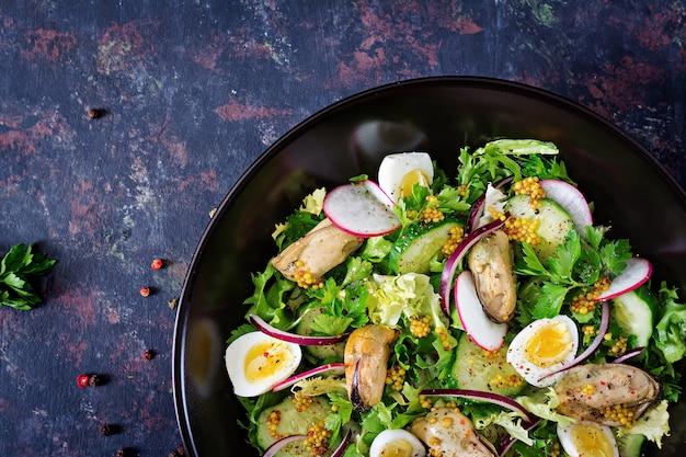 Salada dietética com mexilhões, ovos de codorna, pepino, rabanete e alface. comida saudável. salada de frutos do mar. vista do topo. postura plana.