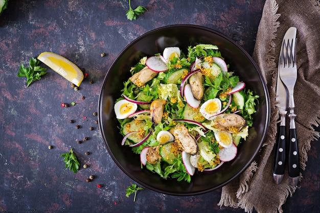 Salada dietética com mexilhões, ovos de codorna, pepinos, rabanete e alface. salada de frutos do mar.