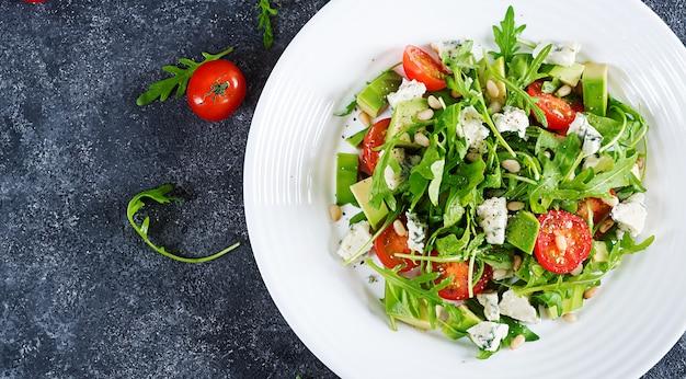Salada dietética com tomates, queijo azul, abacate, rúcula e pinhões. vista do topo. lay plana.