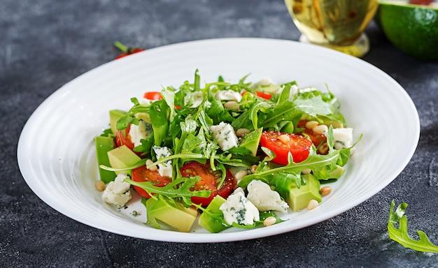 Salada dietética com tomates, queijo azul, abacate, rúcula e pinhões.