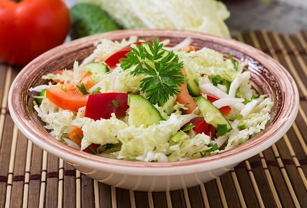 Salada dietética com vegetais frescos (repolho, pimenta, tomate, pepino) em uma tigela de cerâmica