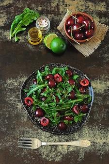 Salada dietética saudável com cerejas doces e arugula. salada de fitness. dieta crua.