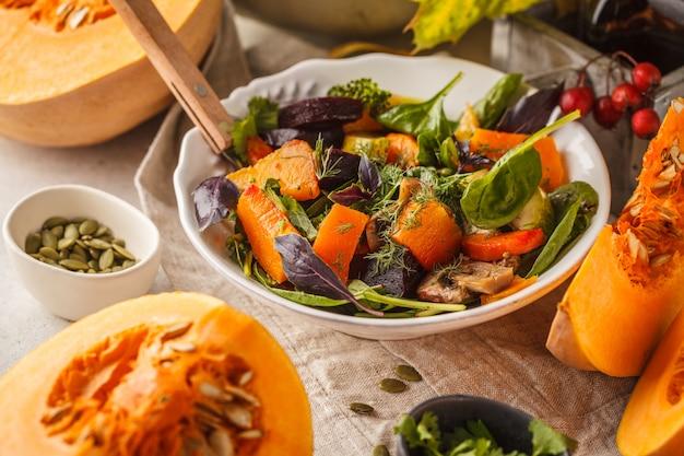 Salada do outono da abóbora, da beterraba, do abobrinha e de cenouras cozidos. conceito de comida saudável vegan.
