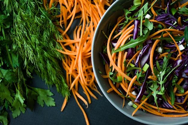 Salada do repolho vermelho, das cenouras e dos verdes. decorado com legumes fatiados e ervas. tiras de corte.