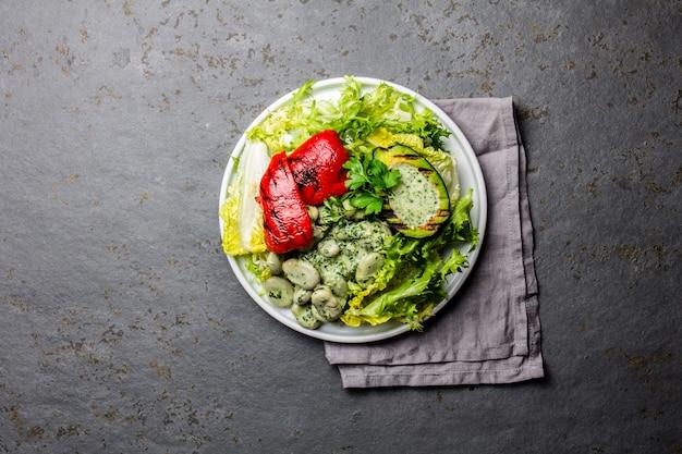 Salada dos feijões da alface do vegetariano com abacate e pimenta de sino grelhados. vista do topo