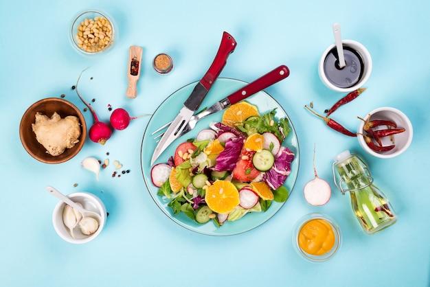 Salada dos legumes frescos com o vário molho no fundo azul, vista superior, beira.