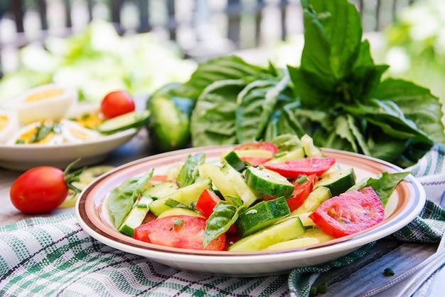 Salada dos tomates e dos pepinos com cebolas verdes e manjericão.