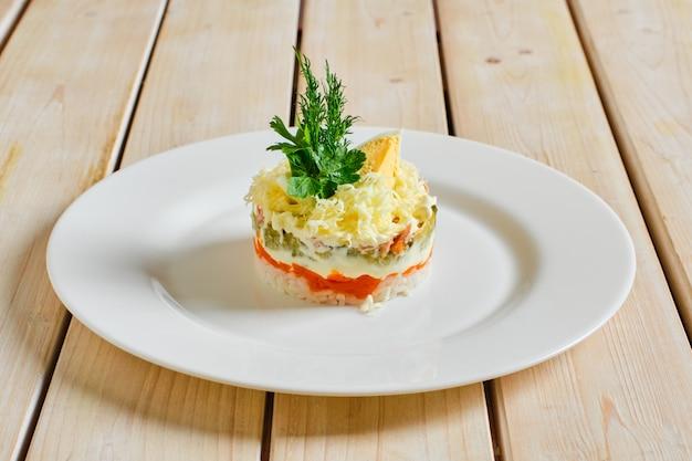 Salada em camadas com arroz, cenoura, pepino em conserva, carne desfiada e queijo