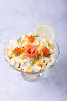 Salada em camadas com truta salgada (salmão), caviar, ovos e vegetais. prato tradicional, uma porção em taça de vidro sobre fundo cinza. fechar-se.