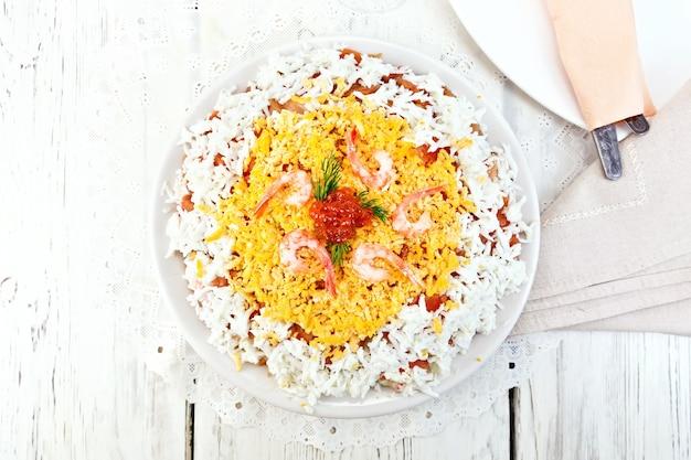 Salada em camadas de salmão, lula, camarão, abacate, arroz e ovos em um prato contra o pano de fundo de pranchas de madeira no topo