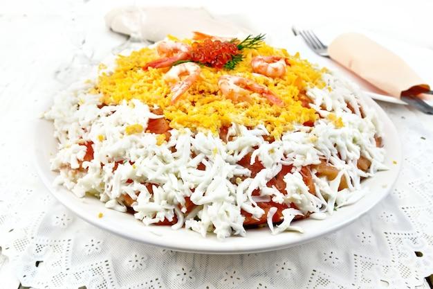 Salada em camadas de salmão, lula, camarão, abacate, arroz e ovos em um prato nas placas de madeira de luz de fundo