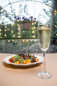Salada em um prato branco com vinho branco