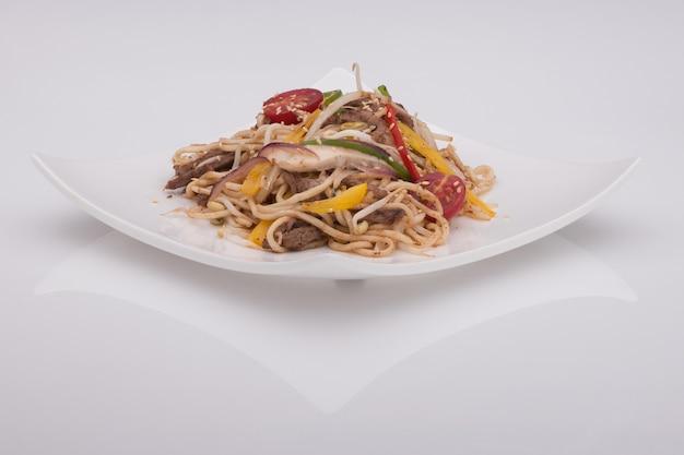 Salada em um prato branco sobre um fundo branco