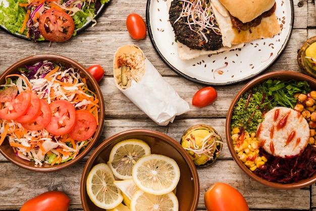 Salada; fatias de limão com hambúrguer; tigela de burrito e envoltório na mesa