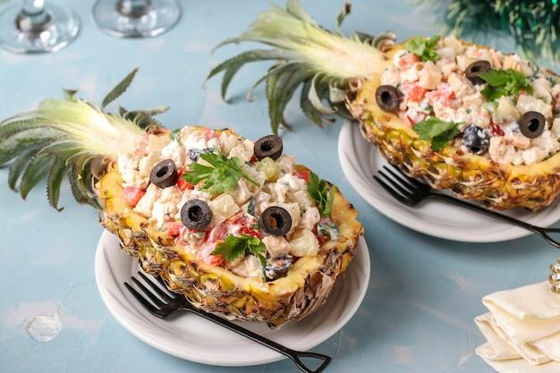 Salada festiva com frango ao meio de abacaxi em uma superfície azul clara, ano novo, dia dos namorados, jantar romântico, closeup, orientação horizontal