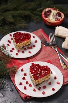 Salada festiva em camadas em forma de coração, decorada com sementes de romã em uma superfície escura, orientação vertical, closeup