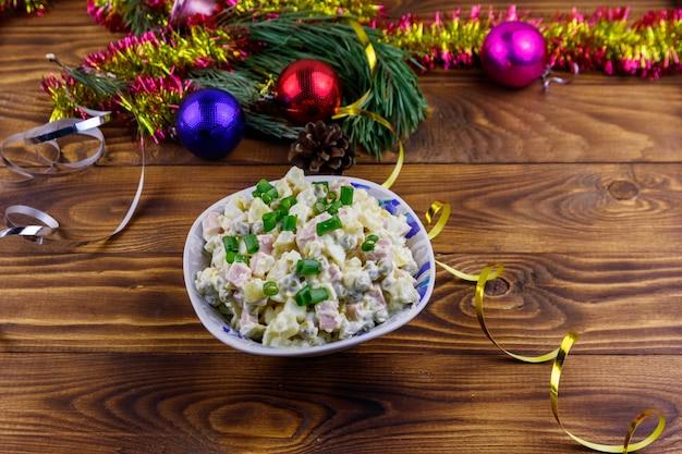 Salada festiva russa tradicional olivier e decorações de ano novo na mesa de madeira