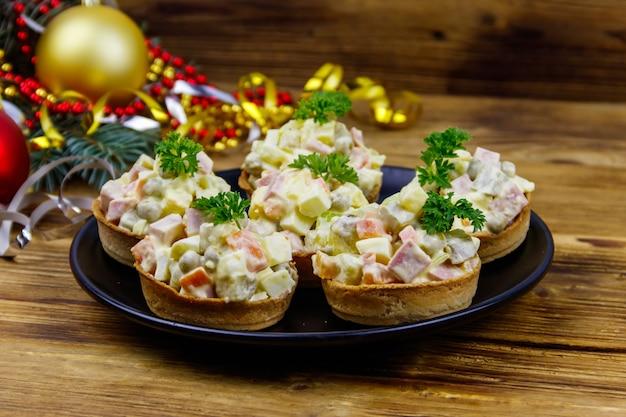 Salada festiva russa tradicional olivier em tortinhas e enfeites de natal na mesa de madeira