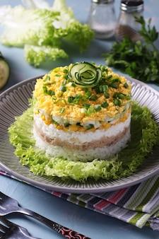 Salada folhada festiva com fígado de bacalhau, arroz, ovos, milho e pepino em um prato sobre fundo azul claro. formato vertical