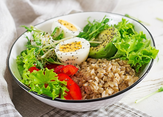 Salada fresca. bacia do café da manhã com farinha de aveia, paprika, abacate, alface, microgreens e ovo cozido. comida saudável. tigela de buda vegetariano.
