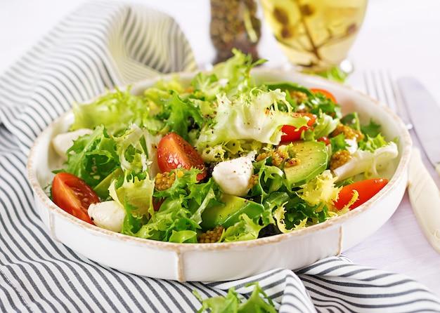 Salada fresca com abacate, tomate, azeitonas e mussarela em uma tigela. comida de fitness. refeição vegetariana.