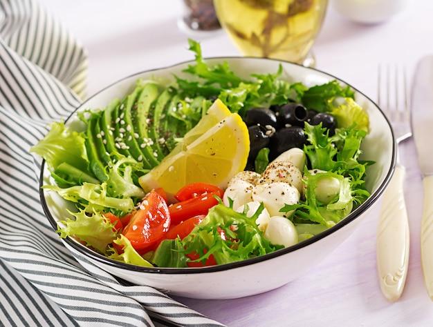 Salada fresca com abacate, tomate, azeitonas e mussarela em uma tigela