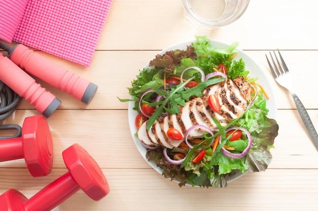 Salada fresca com equipamentos de exercício de frango e fitness na mesa de madeira