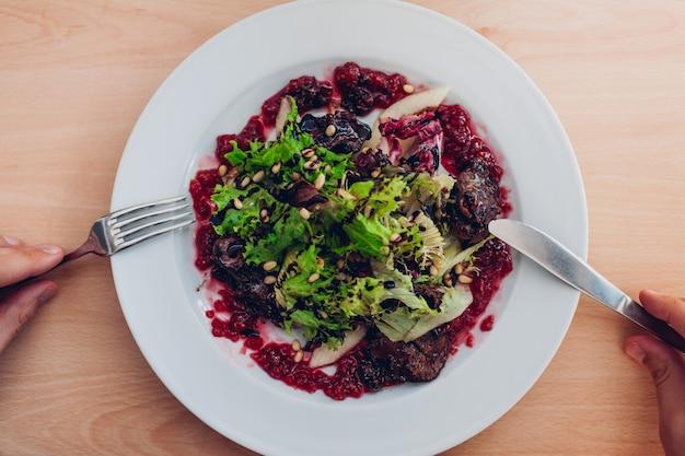 Salada fresca com fígado, framboesas, pêra, alface e pinhão no almoço. homem comendo em restaurante